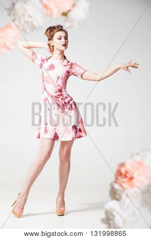 Portrait of young woman in dress with floral print posing against of white background.Flowers decorate shot frame