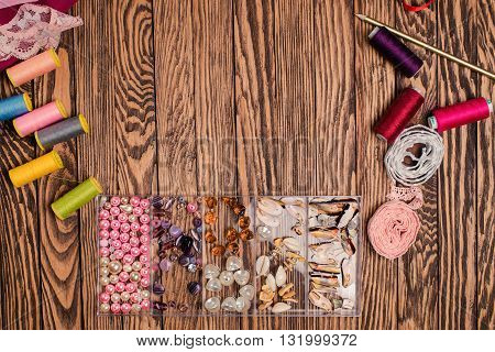 Set for needlework placed on wooden background materials and tools.Top view.A lot of copyspace.