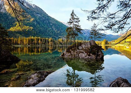 View on turquoise water and scene of trees on a rock island at Lake Hintersee. Location famous resort National park Berchtesgadener Land, Ramsau, Bavaria, Alps.