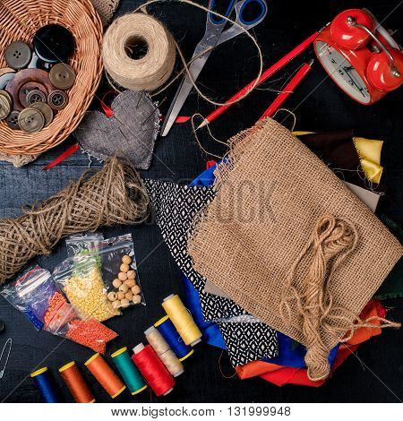 Set for needlework placed on the black background materials and tools.Top view.