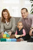 stock photo of nuclear family  - Happy family playing on floor with baby girl at home - JPG