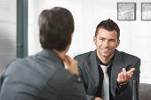 Постер, плакат: Молодой предприниматель сидя на диване в офисе разговаривать предприниматель улыбаясь