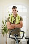 foto of personal trainer  - Personal trainer wearing sportswear and towel standing in living room at home with training bike - JPG