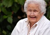 stock photo of elderly woman  - sweet elderly lady joyfully smiling while taking a break from reading - JPG