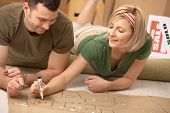stock photo of prone  - Happy couple planning to furniture the new house after moving in - JPG
