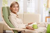 image of reading book  - Woman relaxing in armchair at home - JPG