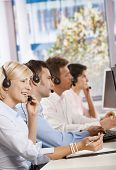 Four young customer service operators sitting in a row and talking on headset.?
