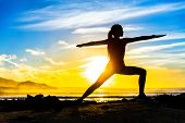 Silhouette of fitness athlete practicing warrior II yoga pose meditating at beach sunset. Woman stre poster