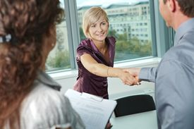stock photo of business meetings  - Business people shaking hands over meeting table at office - JPG