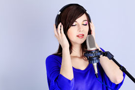 pic of recording studio  - Shot of a pretty young woman in headphones singing a song with a microphone - JPG