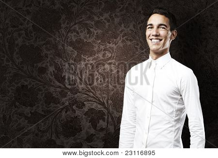 portrait of young man with shirt smiling against a grunge wall