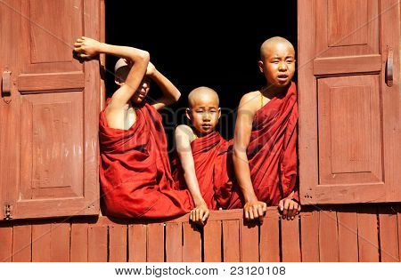 INLE LAKE, MYANMAR - FEBRUARY 02: Unidentified young monks look out of a monastery window on February 02, 2011 in Shwe Yaunghwe monastery in Nyaungshwe, Shan state of Myanmar