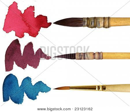 3 brushes with different colours of paint, isolated on white background