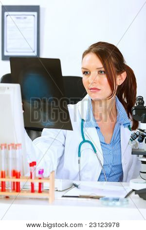 Doctor Woman Sitting At Office Table And Analyzing Patients Roentgen