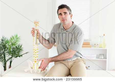 Chiropractor Holding The Model Of A Spine