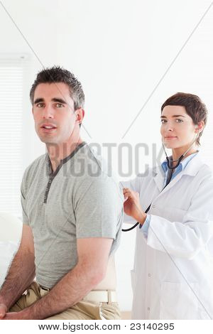 Cute Doctor Examining A Patient With A Stethoscope
