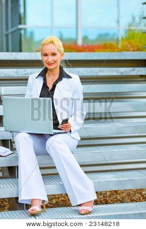 Happy Business Woman Sitting On Stairs At Office Building And Working On Laptop