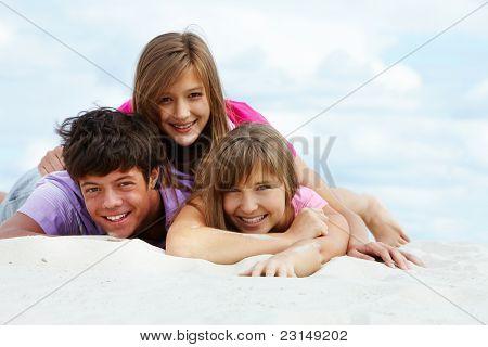 Portrait of three teenage friends on sandy beach