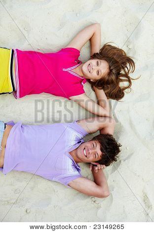 Above angle of joyful teenage couple lying on sandy beach