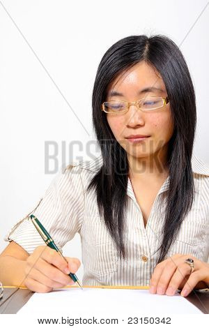 Chinese Businesswoman, Sitting At Desk Writing