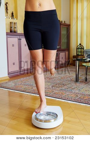 Feet of a woman on bathroom scale