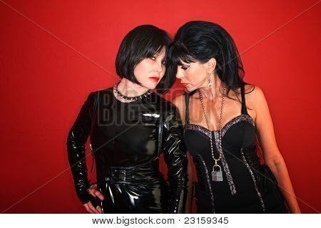 Two Sexy Dominatrix Women Pose On Red