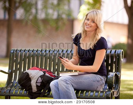 Friendly young female student sitting on a bench sending a text message