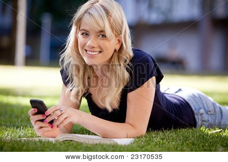 Happy university student sending a text message