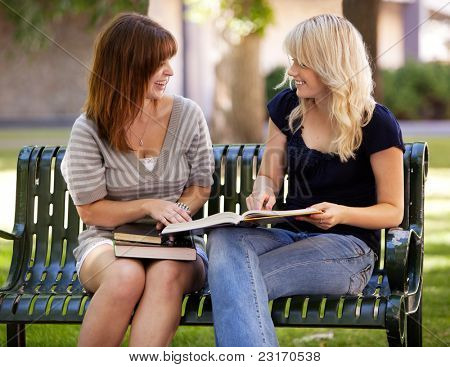 Portrait of two university students studying outdoors on a park bench