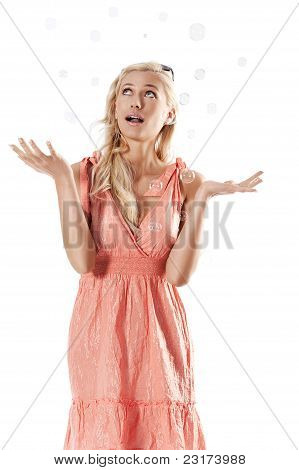 Blond Beautiful Girl Standing Against White Background Looking Towards The Soap Bubbles