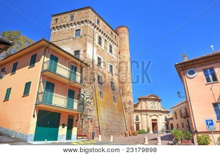 Small plaza surrounded by ancient castle, old church and city hall building in Roddi - small town in Piedmont, northern Italy.
