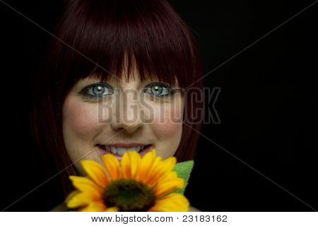 Girl Smiling Behind Sunflower