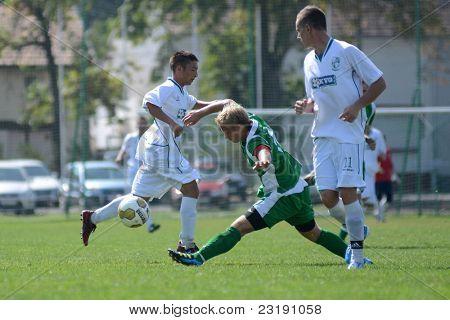 KAPOSVAR, HUNGARY - SEPTEMBER 5: Daniel Vaszilko (white 11) in action at the Hungarian National Championship under 19 game Kaposvar (white) vs. Nagyatad (green) September 5, 2011 in Kaposvar, Hungary.