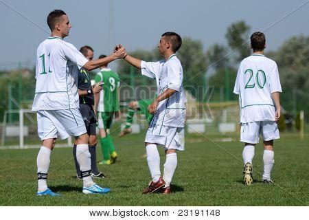 KAPOSVAR, HUNGARY - SEPTEMBER 5: Kaposvar players celebrate a goal at the Hungarian National Championship under 19 game Kaposvar (white) vs. Nagyatad (green) September 5, 2011 in Kaposvar, Hungary.
