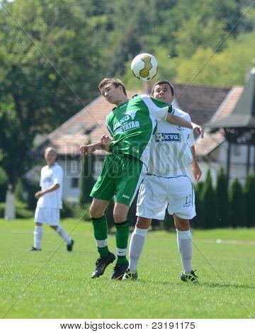 KAPOSVAR, HUNGARY - SEPTEMBER 5: Laszlo Tulok (white 12) in action at the Hungarian National Championship under 19 game Kaposvar (white) vs. Nagyatad (green) September 5, 2011 in Kaposvar, Hungary.