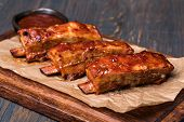 Grilled pork ribs in barbecue sauce on wooden plate poster