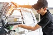 Car Wash Worker Wearing A T-shirt And A Black Cap Is Using A Sponge To Clean The Car In The Car Wash poster