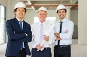 Portrait Of Three Smiling Men In Formalwear And Hard Hats With Blueprint At Site. Team Of Building C poster