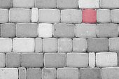 Red Pavement Block Among Black And White Concrete Blocks poster