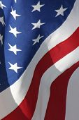 stock photo of american flags  - Vertical Image of American Flag with Stars and Stripes waving in the breeze - JPG