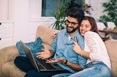 Man Using Laptop And Woman Holding Credit Card. Young Couple Shopping Online With Credit Card At Hom poster
