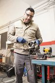 Man Mechanic Working In Mechanic Workshop Looking To Camera poster
