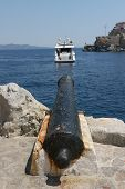stock photo of trebuchet  - Old iron cannon pointing across the sea to a boat - JPG