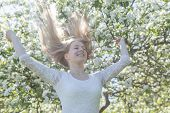 A Teenager Stands Near An Apple Tree In A Blossoming Apple Orchard On A Spring Sunny Day And Enjoys  poster