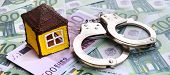 Small Toy House And Handcuffs Is Lies On A Set Of Green Monetary Denominations Of 100 Euros. A Lot O poster
