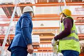 Back View Low Angle Portrait Of Warehouse Manager And Factory Worker Looking Up At Tall Storage Shel poster