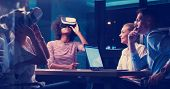 Multiethnic Business team using virtual reality headset in night office meeting  Developers meeting  poster