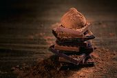 Assortment Of Dark And Milk Chocolate Stack, Truffles. Chocolate With Cocoa Powder On Dark Rustic Wo poster
