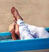 image of wedding couple  - pair of legs in the boat on the beach - JPG