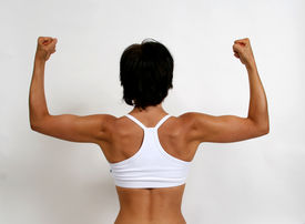 stock photo of athletic woman  - A tanned woman flexing her arm muscles - JPG